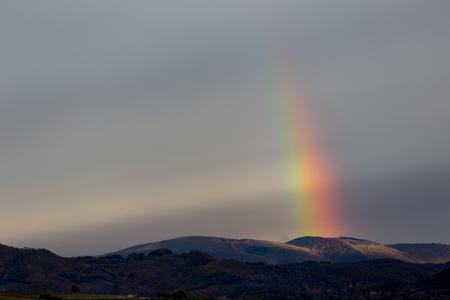 いくつかの丘の上に虹の一部の美しくシュールな景色 写真素材 - 107165494