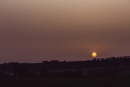 Sunset with sand suspended in the atmosphere, coluring the sky red, over some hill and trees silhouettes Stock Photo