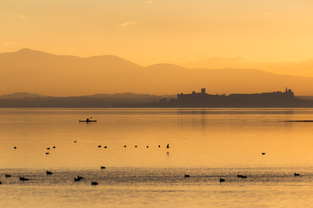 Beautiful view of Trasimeno lake (Umbria, Italy) at sunset, with orange tones, birds on water, a man on a canoe and Castiglione del Lago town on the background 스톡 콘텐츠