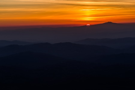 Beautiful sunset with sun coming down behind various layers of mountains