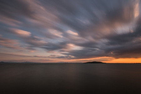 Beautiful wide angle, long exposure view of a lake at sunset, with an huge sky with moving clouds 版權商用圖片