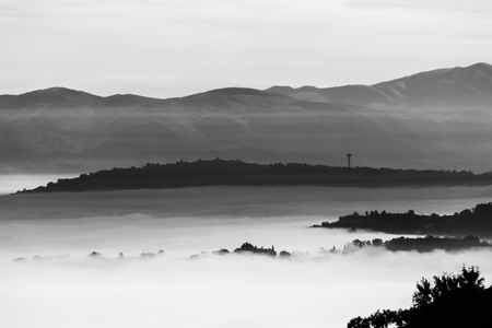 Fog filling a valley in Umbria (Italy), with layers of mountains and hills, trees in the foreground and Montefalco town at the distance