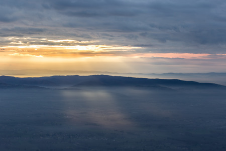 Sun rays coming down from some clouds over a valley filled by fog, illuminating part of it