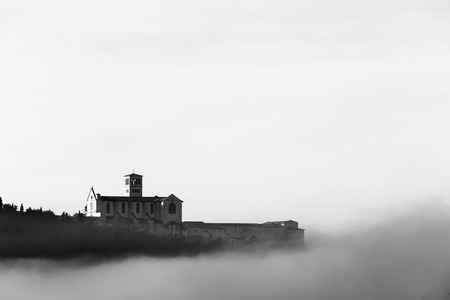 A view of St.Francis church in Assisi in the middle of mist beneath a deep sky with clouds