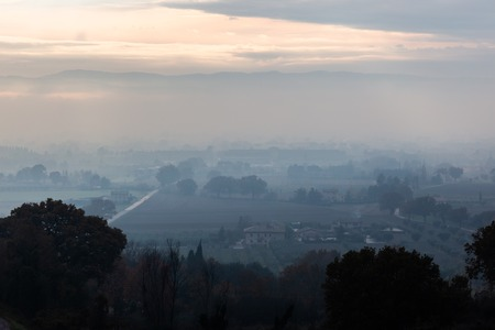 Moody view of Umbria valley (Italy) in the midst of autumn mist Imagens