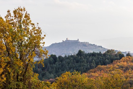 Beautiful view of Assisi town (Umbria) and St.Francis church in autumn from an unusual place, behind an hill with orange and yellow trees