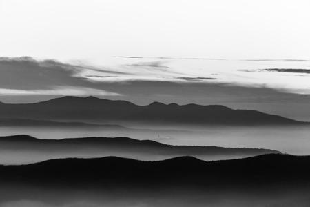 Nebel füllt ein Tal in Umbrien (Italien), mit Schichten von Bergen und Hügeln