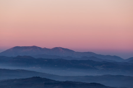 Beautifully colored sky at dusk, with mountains layers and mist between them Reklamní fotografie