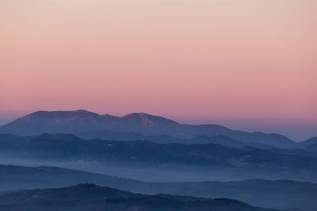 Cielo de bellos colores al anochecer, con capas de montañas y niebla entre ellas