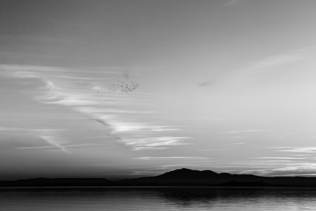 Beautiful view of Trasimeno lake (Umbria, Italy) at sunset, with cloud shapes on the sky Imagens