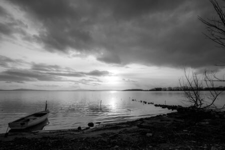 Beautiful view of Trasimeno lake shore (Umbria) at sunset, with a little boat, skeletal tree and sun coming down