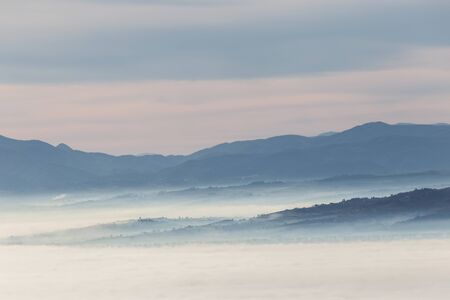 Fog filling a valley in Umbria (Italy) at dawn, with layers of mountains and hills and various shades of blue. Imagens