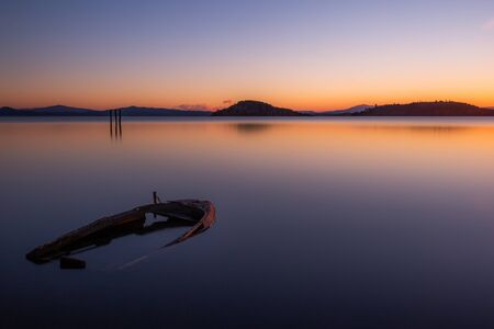 An almost completely sinked little boat in Trasimeno lake (Umbria, Italy) at dusk.