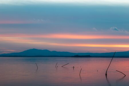 Sunset a Trasimeno lake (Umbria, Italy), with poles on the foreground