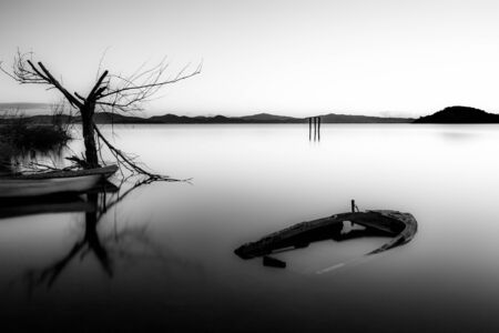 An almost completely sinked little boat in Trasimeno lake (Umbria, Italy) at dusk, near a skeletal tree