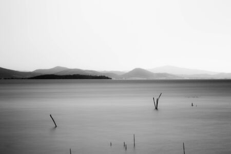 Beautiful long exposure view of Trasimeno Lake (Umbria, Italy), with still water and branches