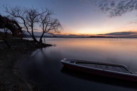 An empty little boat in Trasimeno lake (Umbria, Italy) at dusk, near a skeletal tree