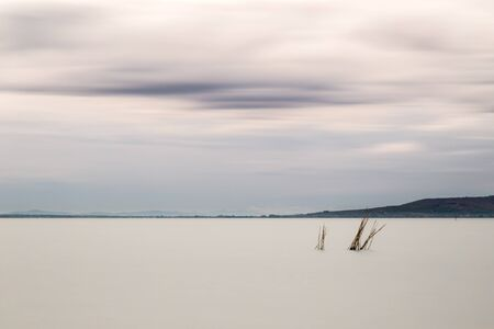 Beautiful long exposure view of Trasimeno Lake (Umbria, Italy), with still water and moving clouds
