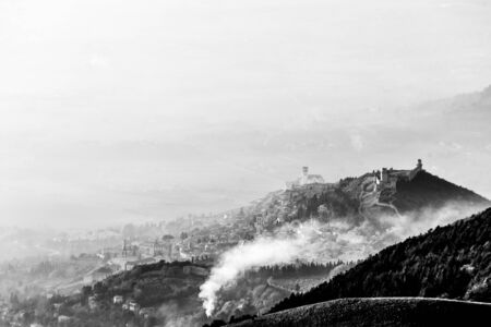 A view from above of Assisi town (Umbria, Italy) in the middle of mist, with smoke on the foreground