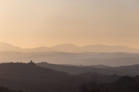 Beautiful view of Tuscany hills at sunset, with mist and warm colors Stock Photo