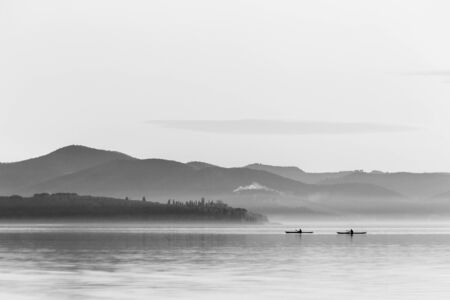 Beautiful view of a lake with two men on canoes 写真素材
