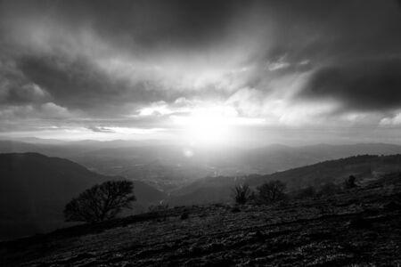Stimmungsvoller Sonnenuntergang auf dem Monte Cucco (Umbrien, Italien), mit Baum im Vordergrund und Sonne, die durch Wolken filtert