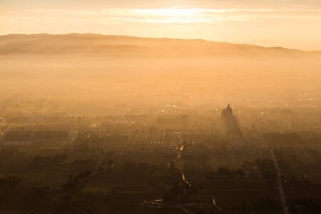An epic, aerial view of Santa Maria degli Angeli church (Assisi)projecting sunrays, and lighting up half of the valley