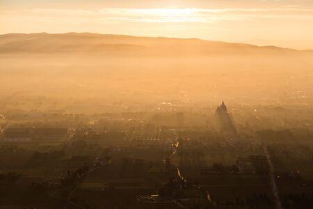 Una vista aérea épica de la iglesia de Santa Maria degli Angeli (Asís) proyectando los rayos del sol e iluminando la mitad del valle Foto de archivo