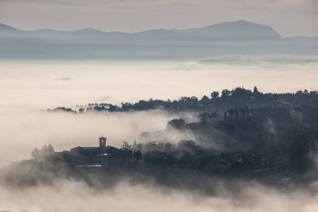 Surreal view of of a little town in Umbria (Italy) almost completely hidden by fog