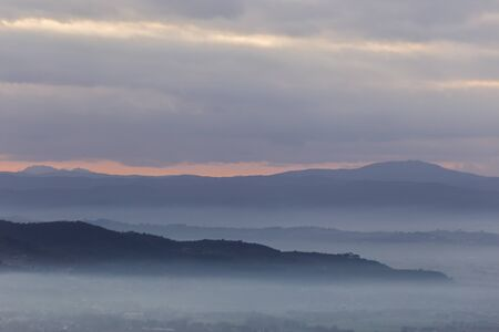 A view of Umbria valley with hills and fog.