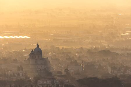 An epic, aerial view of Santa Maria degli Angeli church (Assisi)projecting sunrays with sun lighting up half of the valley.