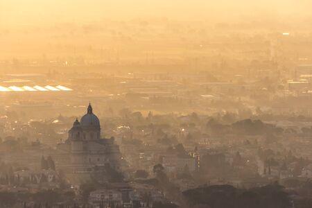 Una vista aérea épica de la iglesia de Santa Maria degli Angeli (Asís) proyectando rayos de sol con luz solar en la mitad del valle.