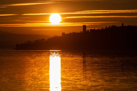 Sunset on Trasimeno lake (Umbria, Italy), with the sun coming down behind Isola Maggiore and beautiful water reflections Standard-Bild