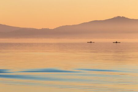 Beautiful view of a lake at sunset, with orange tones and two men on canoes.