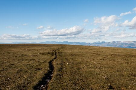 A mountain field with a very long crack going toward the horizon, beneath a deep blue sky with white clouds