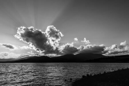 Sunrays through dark clouds above Trasimeno lake (Umbria, Italy) .