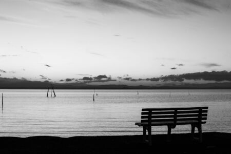 Dusk at Trasimeno lake (Umbria, Italy), with a parking bench on the foreground.