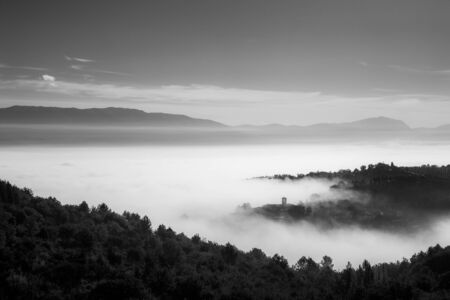 Surreal view of of a little town in Umbria (Italy) almost completely hidden by fog.