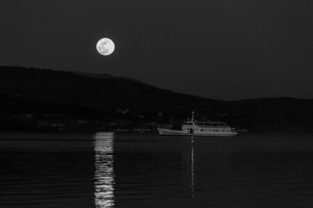 Full moon rising over some hills on a lake, perfectly reflecting on water near an incoming boat.