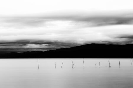 Trasimeno lake (Umbria, Italy), with fishing net poles and branches on perfectly still water.