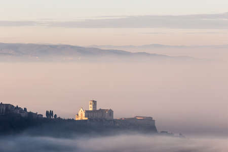 An epic view of St.Francis church in Assisi town (Umbria) above a sea of fog at dawn