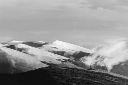 Mountain (Umbria, Italy) in winter, covered by snow, with low clouds and wind turbines.