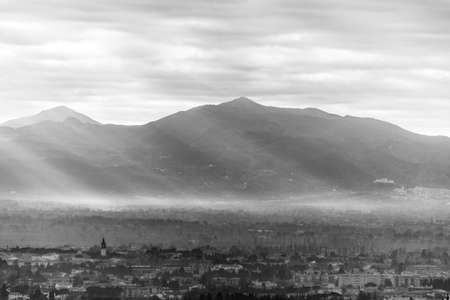 An epic view of Foligno (Umbria) with sunrays lighting up half of the valley in the morning