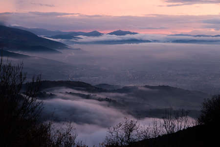 Mist and fog between valley and layers of mountains and hills at dusk, in Umbria (Italy), with city lights underneath