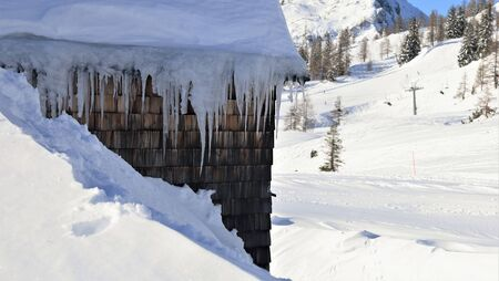 cabin with icicles and snow and skiing lift in background Stock fotó