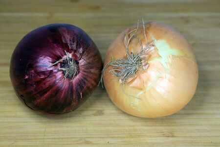 A view looking down on a group of three onions on a worn butcher block cutting board. Reklamní fotografie