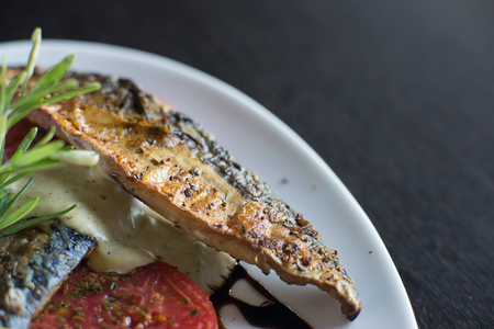 Grilled mackerel with onion plate on wooden table