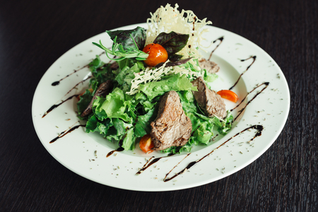 Salad with beef and greens on a white plate