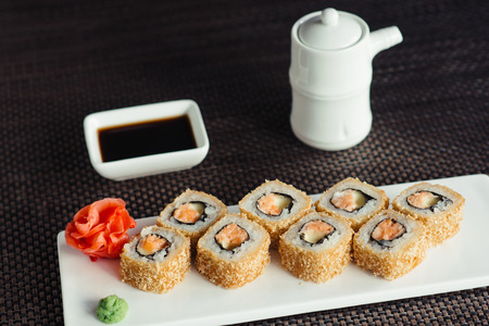 hot sushi on a white plate with chopsticks
