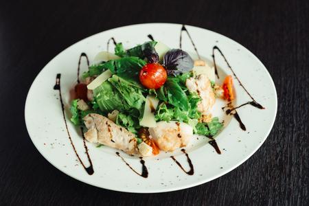 Caesar salad with chicken on white dish